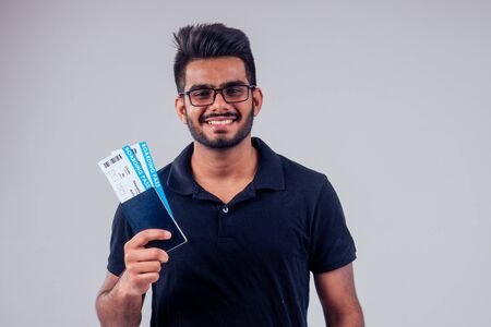 happy indian student male bearded wearing glasses and black t-short holding passport airline ticket yellow studio background . lifestyle summer trip concept