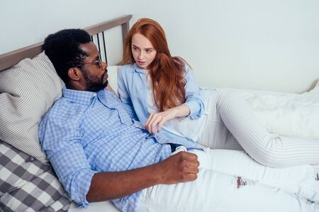 redhaired ginger caucasian happy female and multi-ethnic afro man together lying in bed bedroom.lifestyle tolerance concept