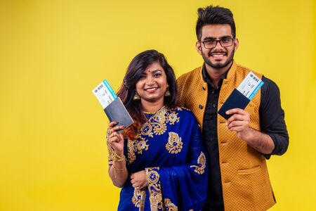 happy tourist couple holding india passport with tickets on yellow background studio