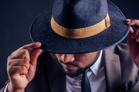 indian business man wearing hat and classic suit on black background in studio