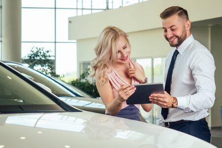 salesman in suit showing catalog to female blonde customer in dealership salon