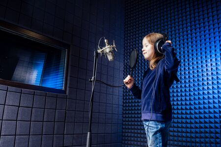 girl star singer artist in a black blouse with headphone recording new song with microphone.