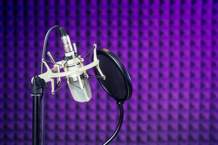 Microphone and headphone in a recording studio soundproof wall Stockfoto