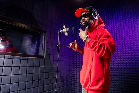 afro american man headphones in a cap and a hood sunglasses recording hip hop song track. 写真素材