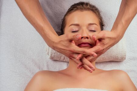 Young woman enjoys ayurvedic facial massage in luxury resort dark lighting