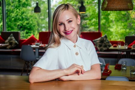 Beautiful rich casual blonde stylish fashion business woman wearing white cotton dress stylish home interior background