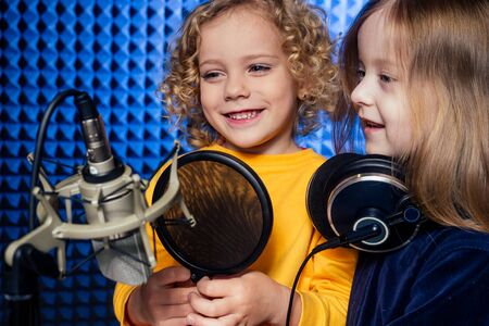 two sisters girls blonde curly hair style star singer artist in a yellow blouse with headphone recording new song with microphone. Stock fotó