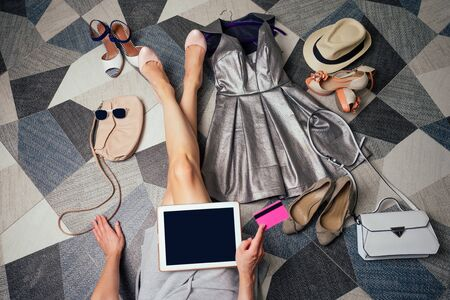beautiful woman smart phone with online shopping app on copy-space display online, shopping at home sitting at floor next to the summer shoes ,straw hat and dress with stylish bag