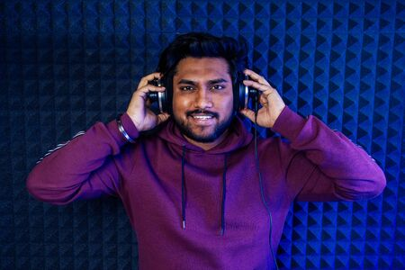 professional singing indian men headphones sound modern studio violet background recording song. dj in nigt club. Stockfoto