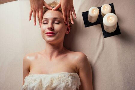 beauty blonde glamour female in spa eyes closed enjoying head massage at spa center professional therapy health stress treatment pampering facial beauty skin:anti acne and anti wrinkles Stock fotó