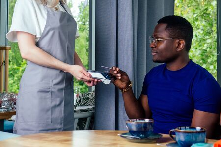 mixed-race friends paying to waiter payment machine in cafe