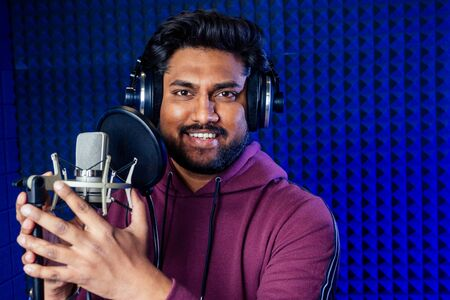 professional singing indian men headphones sound modern studio violet background recording song.