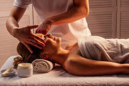 Young woman enjoys ayurvedic facial massage in luxury resort dark lighting. Stock fotó