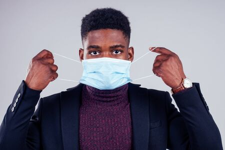 African american male wearing on a gauze mask and warm coat and sweater white background studio. cold season winter autumn or spring. Stock Photo