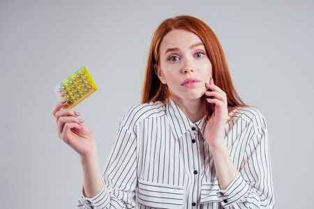 picture of young redhead businesswoman in striped shirt with one pack of pills white background studio Фото со стока