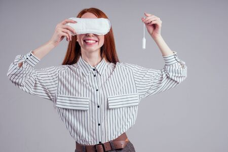 Closeup photo of young redhead businesswoman in striped shirt holding hygiene pad choosing tampon studio white background