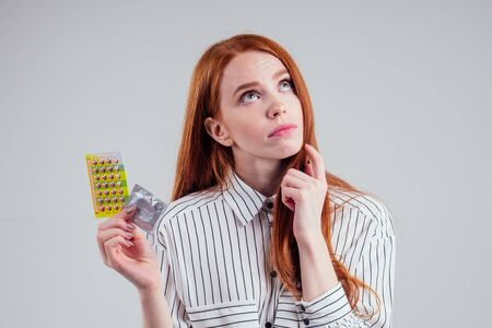 picture of young redhead be lost in thought businesswoman in striped shirt with one pack of pills thinking white background studio