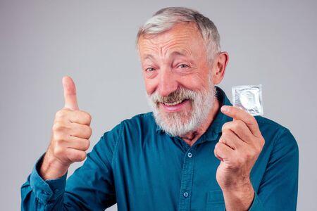 caucasian old senior man holding packed rubber latex condom in studio white background