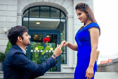 happy asian man in stylish black suit falling knee in front of his beautiful woman in blue long dress asking proposal and giving gold ring on the background of the restaurant street