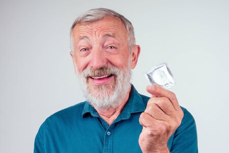 caucasian old senior man holding packed rubber latex condom in studio white background