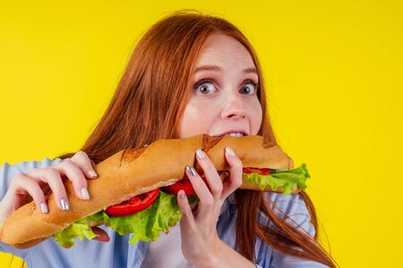 Joyful funny redhaired ginger girl with wild eyes suffering from anarexia with greedy ,eating large sandwic in studio yellow background. eats after 6 pm