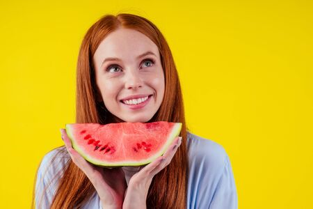 redhaired ginger girl with big piece of watermelon in studio yellow background.detox yoga concept
