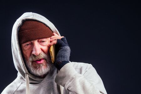 portrait of sad old senior male tramp wearing warm brown hat and leaky gloves,talking by smartphone in studio black background