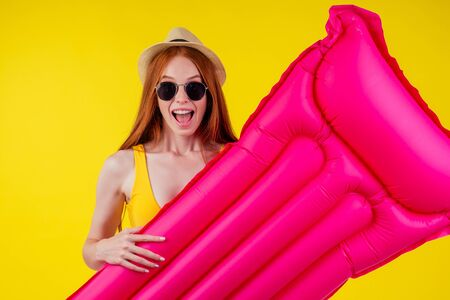 happy redhaired ginger woman ready to pool party,with pink mattress in studio wall yellow background wearing straw hat