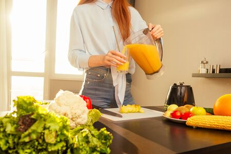 Beautiful redhaired ginger woman making fruits smoothies with blender, preparing drink with bananas, apple and orange at home in kitchen. Фото со стока