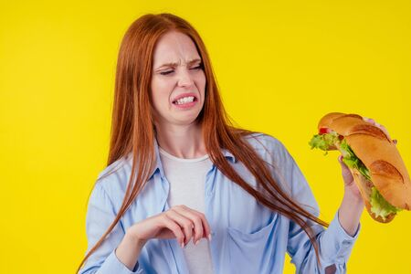 disgust distaste aversion redhaired ginger woman holding huge sandwich with pepper and lettuce salad between bun in studio yellow background