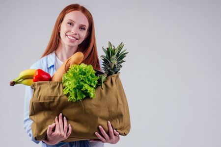 beautiful redhaired ginger woman holding eco cotton shopper bag with fresh fruits,vegetable in wgite studio background Фото со стока