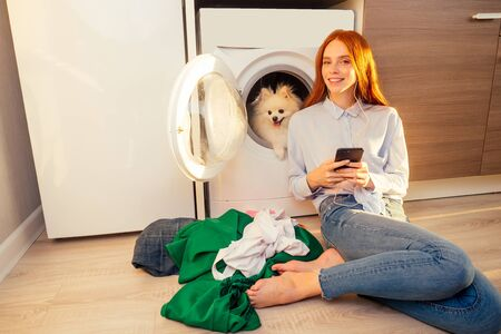 excited funny redhaired girl listening music with headphones,her adorable fluffy spitz inside the washing machine at home a pile of dirty clothes on the floor