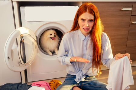Fie, what stench Shocked excited redhaired girl wash pile of dirty smelly clothes ,her adorable fluffy spitz helpinh inside the washing machine at home