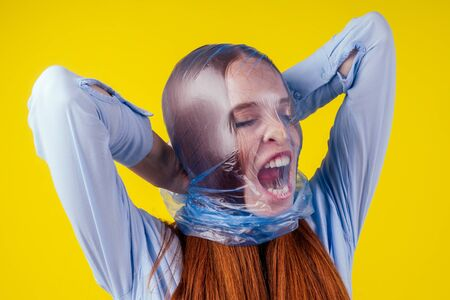 redhaired ginger european woman suffocation head in blue polyethylene package in studio yellow background. eco pollution cellophane film concept