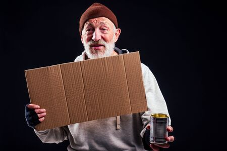 sad man with grey beard wearing leaky gloves and warm brown hat ,holding cardboard copyspase in studio black background