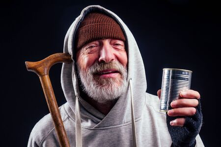 portrait of sad old senior male tramp wearing warm brown hat and leaky gloves,holding metal canned bank jar for money alms in studio black background