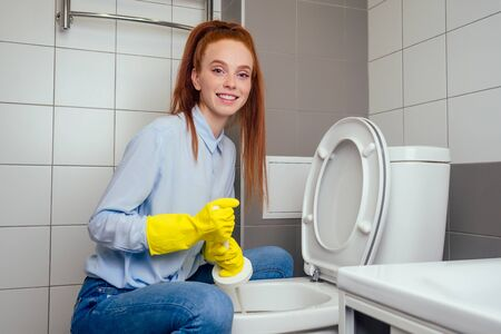 cheereful redhaired ginger woman washing in rest room toilet wearing gloves