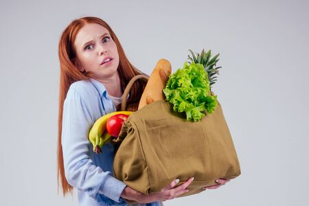 beautiful redhaired ginger woman holding eco cotton bag full of products: banana, pineapple,vegetables