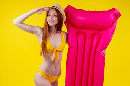 Redhaired ginger female posing floating with inflatable mattress wearing swimmingsuit and hat, looking away at copy space in studio yellow background.Where is water? Stock fotó