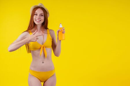 redhaired ginger woman in stylish bikini holding sunscreen bottle making the right choice in studio yellow background