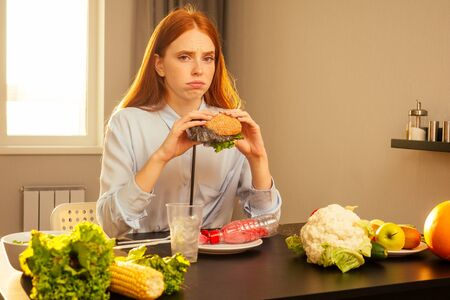 redhaired ginger girl eating fake burger with bun sesame and plastic cellophane film trash,drinking water from disposable cup with non-eco tube at home kitchen