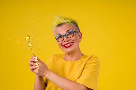 Femme mature avec des cheveux teints en jaune élégant en robe chaude avec des étincelles légères en arrière-plan studio copy spase
