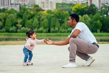 afro father walking the first steps of his mixed race daughter spending time in garden Imagens