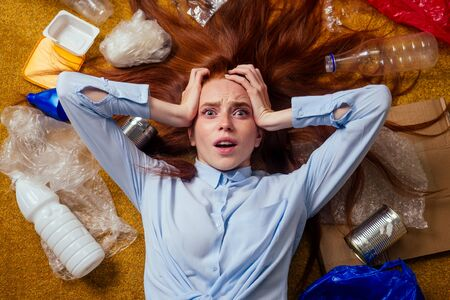 unhappy redhaired ginger girl sorting waste:bottle,paper and plastic lying down at floor carpet and crying