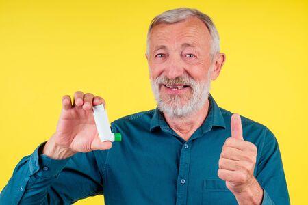 Senior man using an asthma inhaler in studio yellow background