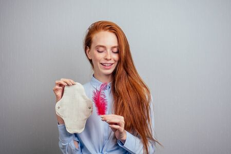 redhaired ginger long hair woman holding eco-friendly organic gaskets made of bio-cotton and disposable tampon.making choice