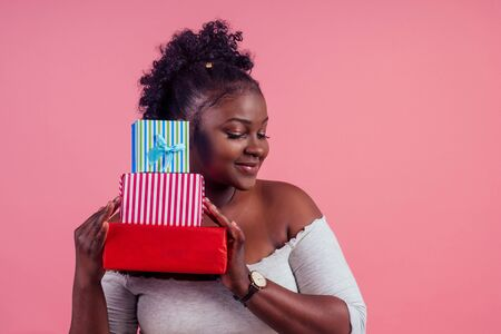 happy afro woman holding gift boxes March 8 in stusio pink background Stock Photo