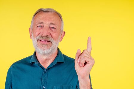 close-up portrait of happy old senior man looking at camera , wearing green cotton shirt with a collar pointing finger up to copy spase in studio yellow background Archivio Fotografico