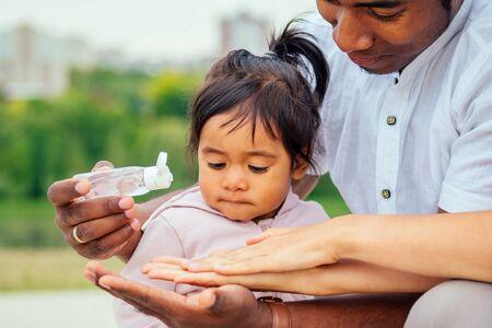 famiglia felice che applica gel antibatterico disinfettante per le mani alle mani della figlia