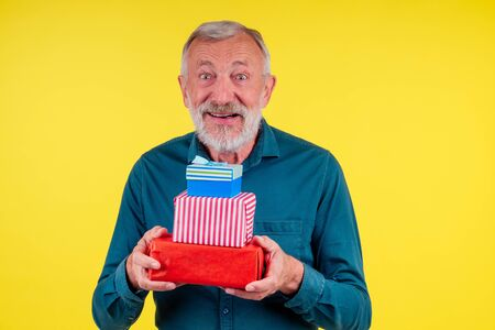 portrait amazed caucasian old elderly man holding two boxex of gifts in studio yellow background Stock Photo
